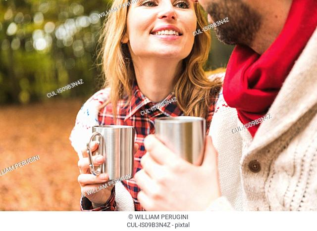 Mid adult couple sitting in park, drinking hot drink from metal cups