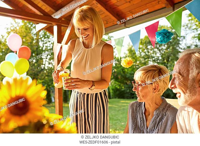 Happy woman serving juice on a garden party