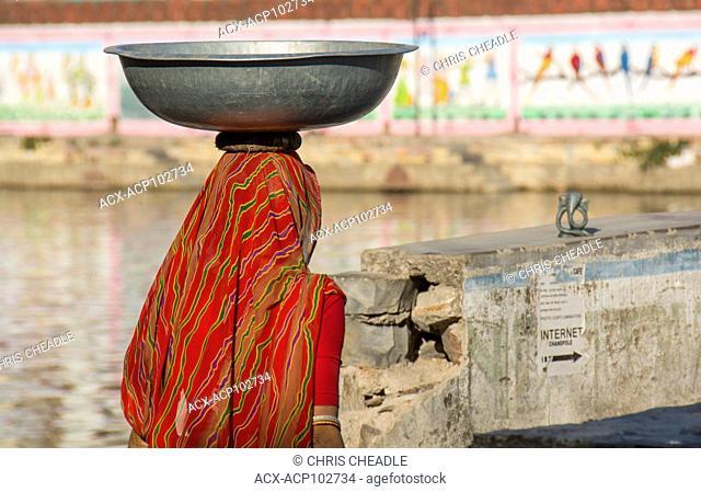 Rajastani woman carries large pan on head, Udaipur, Rajastan, India