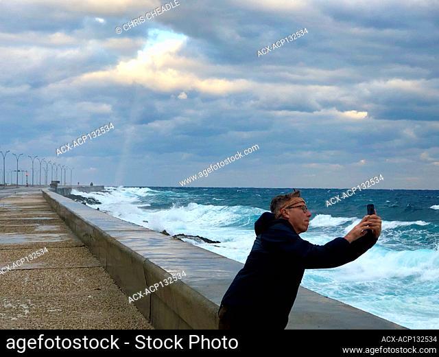 Tourist photographing waves on Malecon, Havana, Cuba
