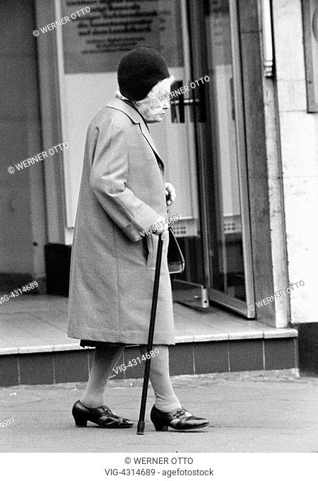 DEUTSCHLAND, OBERHAUSEN, 31.03.1976, Seventies, black and white photo, people, older people, older woman with a walking stick takes a walk
