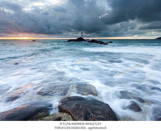 Waves washing over breakwater under stormclouds at sunset, during one of the highest tides of the year, Bude, North Cornwall, England, 18th August 2015