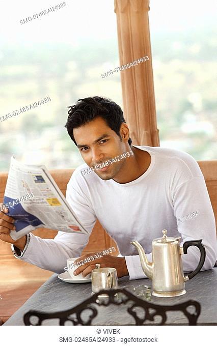 man reading morning newspaper, having hot drink