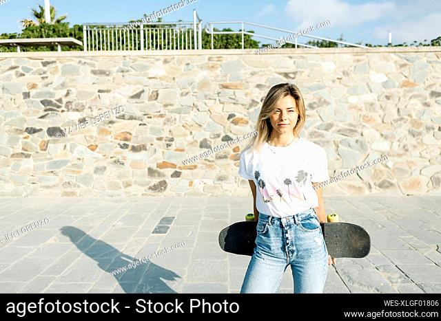 Blond woman with skateboard during sunny day in park