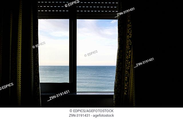 ocean seen through a window with roller blind and curtains, armacao de pera, algarve, portugal
