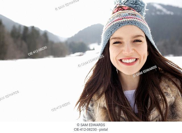 Close up portrait of happy woman wearing knit hat in snowy field