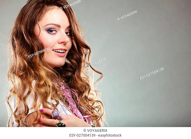 Pretty young woman wearing many plenty of jewelry necklaces beads and rings. Portrait of gorgeous fashion girl in studio on gray