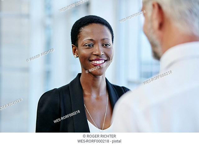 Smiling businesswoman looking at businessman