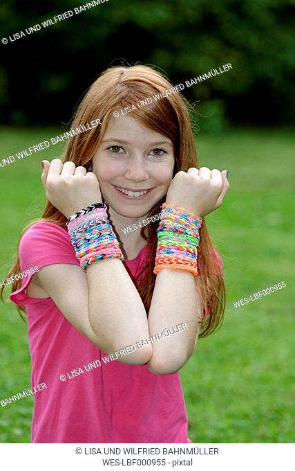 Portrait of happy girl showing self-made looms at her wrists