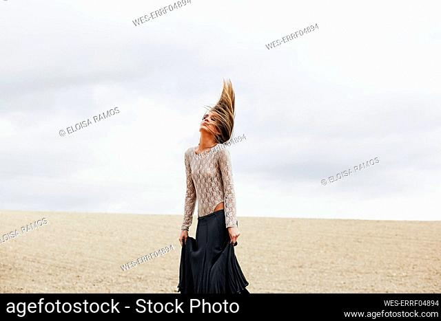Woman wearing skirt tossing hair while standing at beach against sky