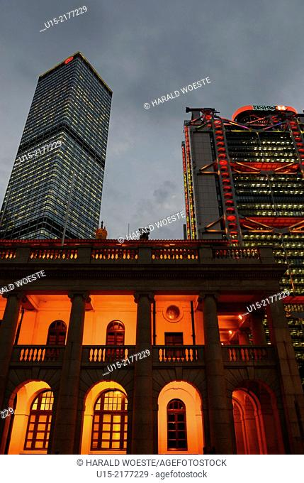 Hong Kong, China, Asia. Hong Kong Central. The two towers of the Cheung Kong Center (left) and the luminous HSBC bank (right)behind the illuminated old building...