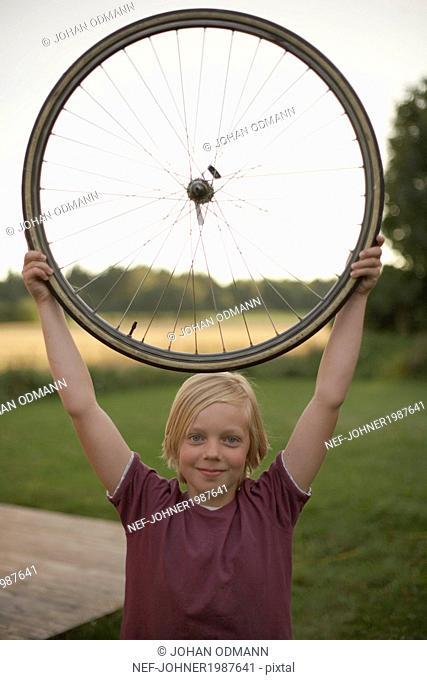 Boy holding bicycle wheel