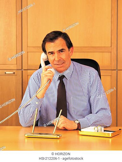 Businessman talking over phone while sitting in office