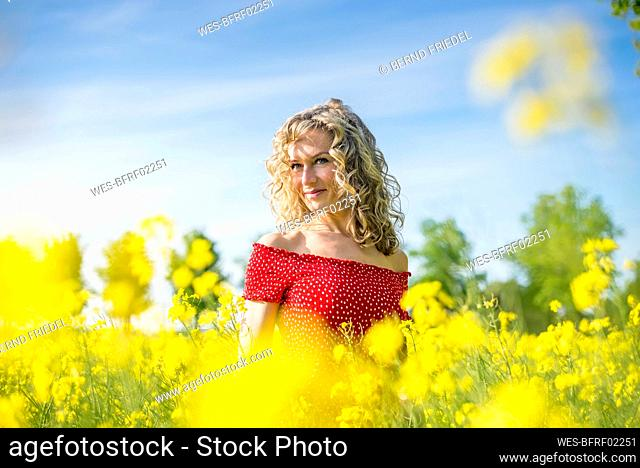 Beautiful woman wearing red dress looking away while standing amidst oilseed rapes