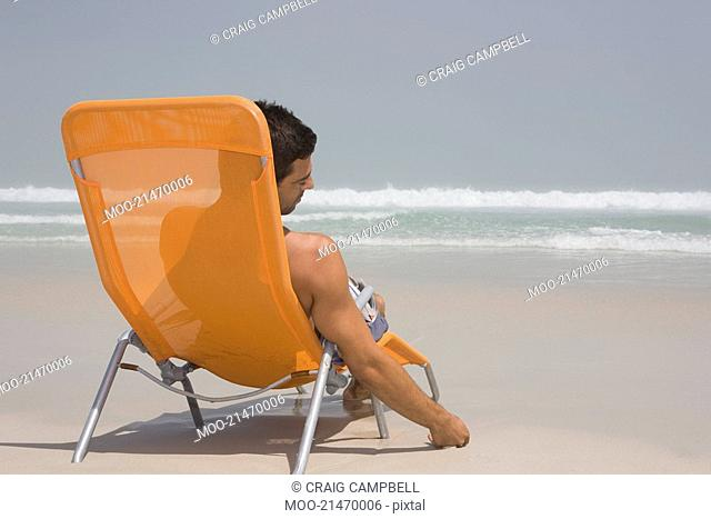 Man sitting on deckchair at beach contemplating