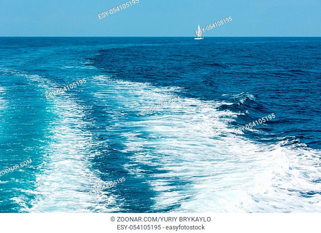 Trace tail of speed boat or ferry on water surface in the sea and white sailing vessel in far. Natural and vacation background