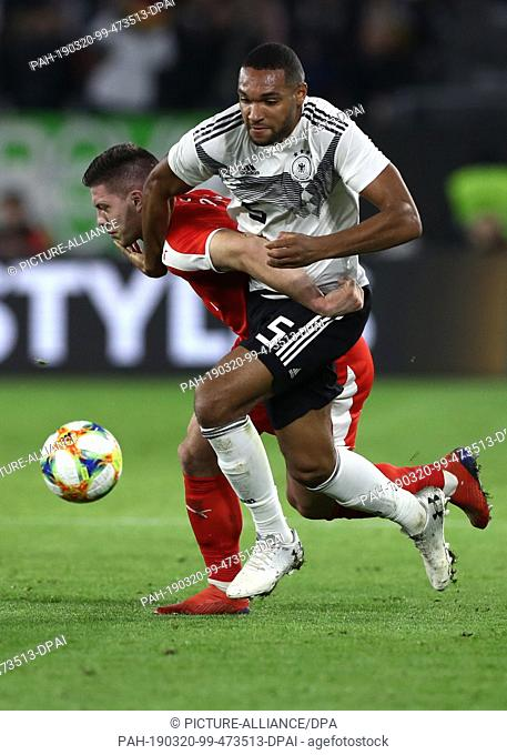 20 March 2019, Lower Saxony, Wolfsburg: Soccer: International match, Germany - Serbia in the Volkswagen Arena. Jonathan Tah from Germany and Luka Jovic from...