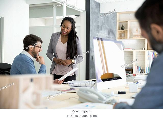Architects discussing paperwork in office