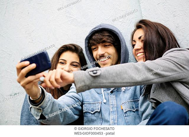 Three friends taking a selfie with cell phone