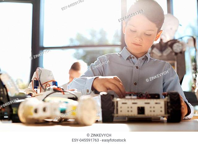 Young creator. Handsome little boy sitting at the table full of robot parts and being busy with construction of his own robotic vehicle