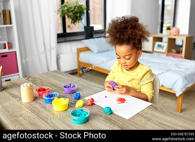 little girl with modeling clay playing at home