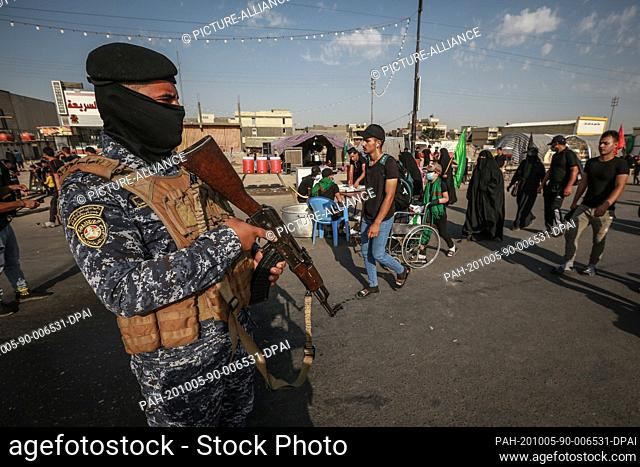 05 October 2020, Iraq, Karbala: A member of the Iraqi security forces (R) observes Shia Muslims march from Baghdad to visit the the Husayn Mosque in Karbala on...