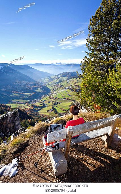 Hiker resting on a bench at Mt Herrensteig, Valle di Funes at back, South Tyrol, Italy, Europe