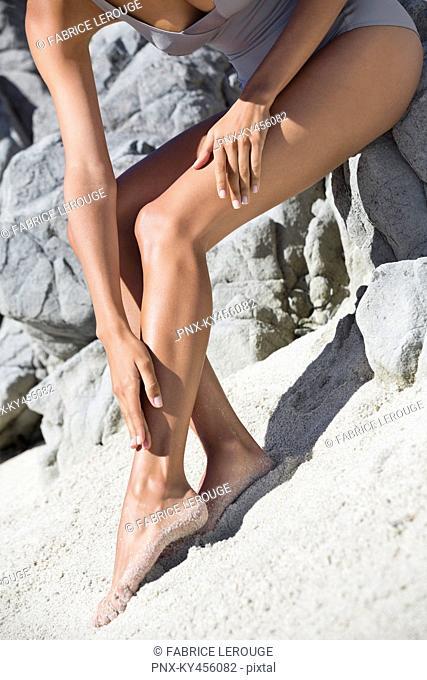 Woman applying suntan lotion on her leg on the beach