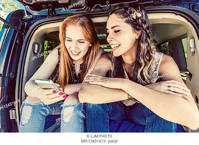 Two young women on a road trip sit in the back of a vehicle using a smart phone; Edmonton, Alberta, Canada