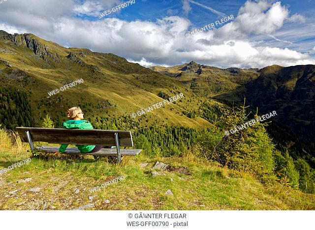 Austria, Carinthia, Drau Valley, woman sitting on bench in mountain landscape