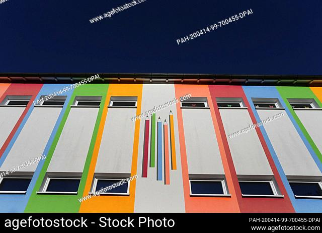 14 April 2020, Bavaria, Bad Wörishofen: Coloured pencils are painted on the colourful facade of the parish Kneipp primary and secondary school