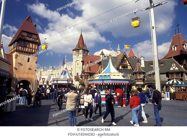 Disney World, Fantasyland, Orlando, Florida, FL, Magic Kingdom, Lake Buena Vista, Crowd of people walk along the street in Fantasyland with the scenic skyway...