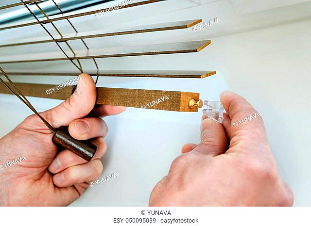 Installing wooden blinds. Man attaches the plastic braket to the bottom plank
