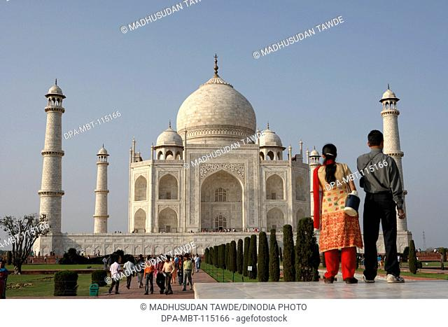 Young couple viewing at Taj Mahal Seventh Wonders of World on the south bank of Yamuna river , Agra , Uttar Pradesh , India UNESCO World Heritage Site