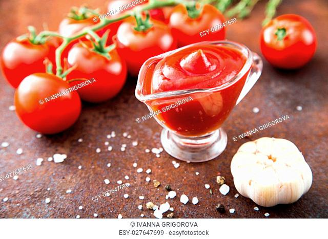 Tomato ketchup sauce with garlic, spices and herbs with cherry tomatoes in a glass bowl on stone table, selective focus