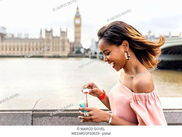 UK, London, happy woman making soap bubbles near Westminster Bridge