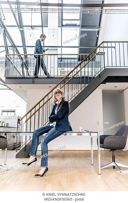 Businesswoman sitting on desk in office with businessman walking on upper floor