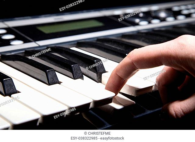 Playing on piano keyboard on black background
