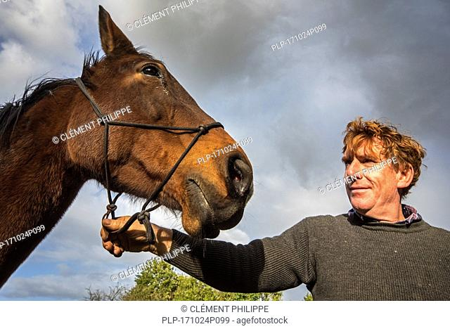 Close up portrait of smiling man / owner holding brown warmblood horse outdoors