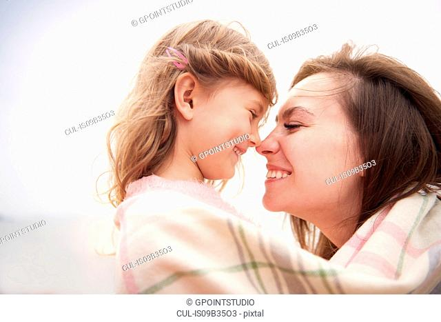 Happy mother and daughter wrapped in blanket, rubbing noses