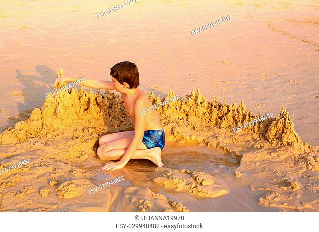 preteen boy playing with sand construct castle on the beach close up photo
