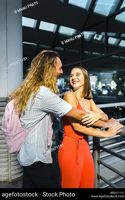 Smiling couple looking face to face while standing at train station