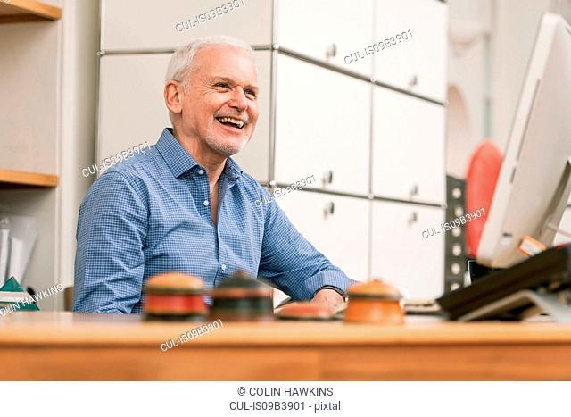 Senior man smiling at work desk