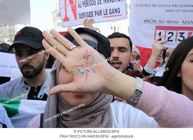12 March 2019, Algeria, Algiers: An Algerian student takes part in a protest one day after President Abdelaziz Bouteflika announced his withdrawal from the...