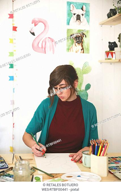 Artist drawing with green pencil on paper