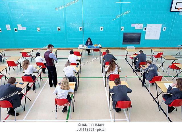 Teachers supervising middle school students taking examination at desks in school gymnasium