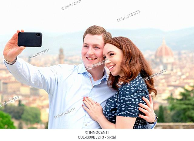Young couple taking selfie, Santa Maria del Fiore in background, Florence, Toscana, Italy
