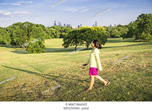 Asian woman walking in urban park
