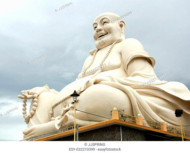 Big Buddha statue over cloudy sky in a Buddhist Temple in Vietnam