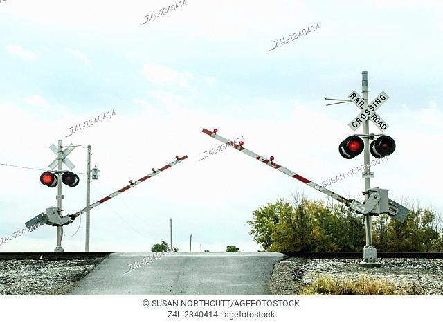 Train rail crossing arms coming down. Lights flashing